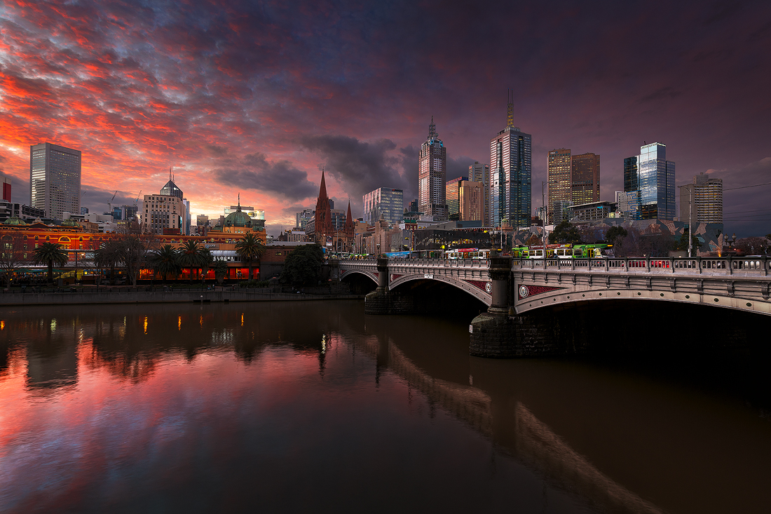 The buildings of Melbourne witness a fiery sunset over the Yarra River.